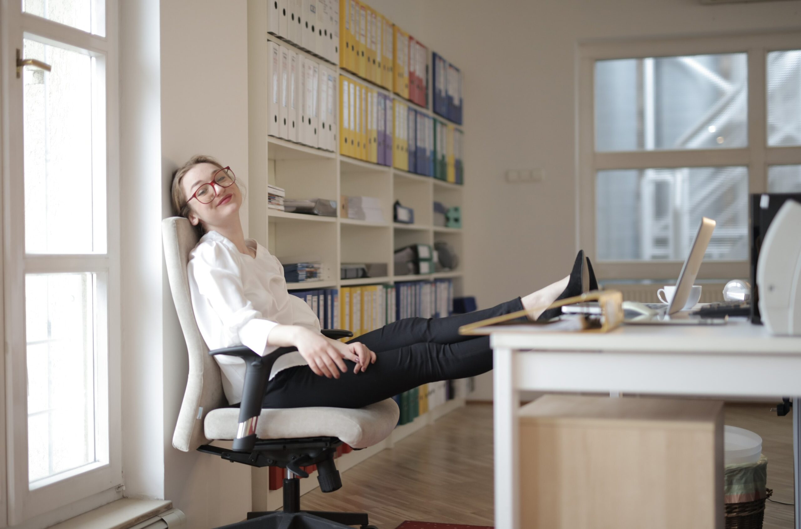 woman sitting at desk with feet on table