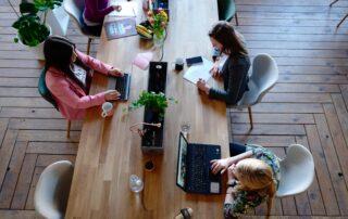 three women sat at desk on laptops
